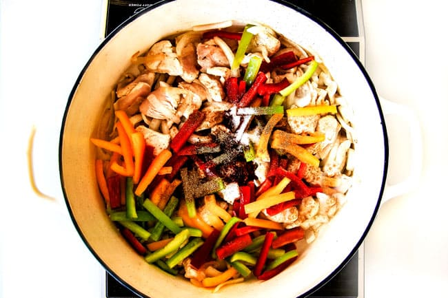 showing how to make chicken fajita pasta by adding chicken, bell peppers, onions and fajita seasonings to a large pot