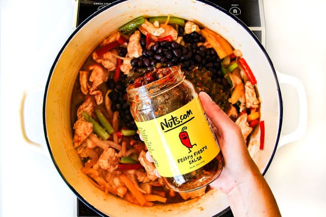 showing how to make best fajita chicken pasta by adding salsa to pot with chicken and bell peppers