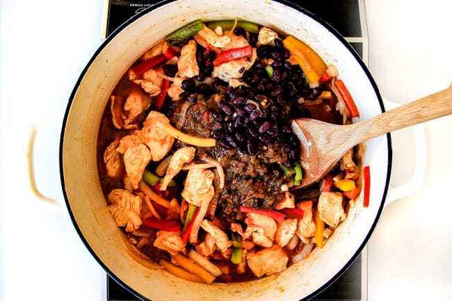 showing how to make easy chicken fajita pasta by adding black beans to chicken, bell peppers and onions
