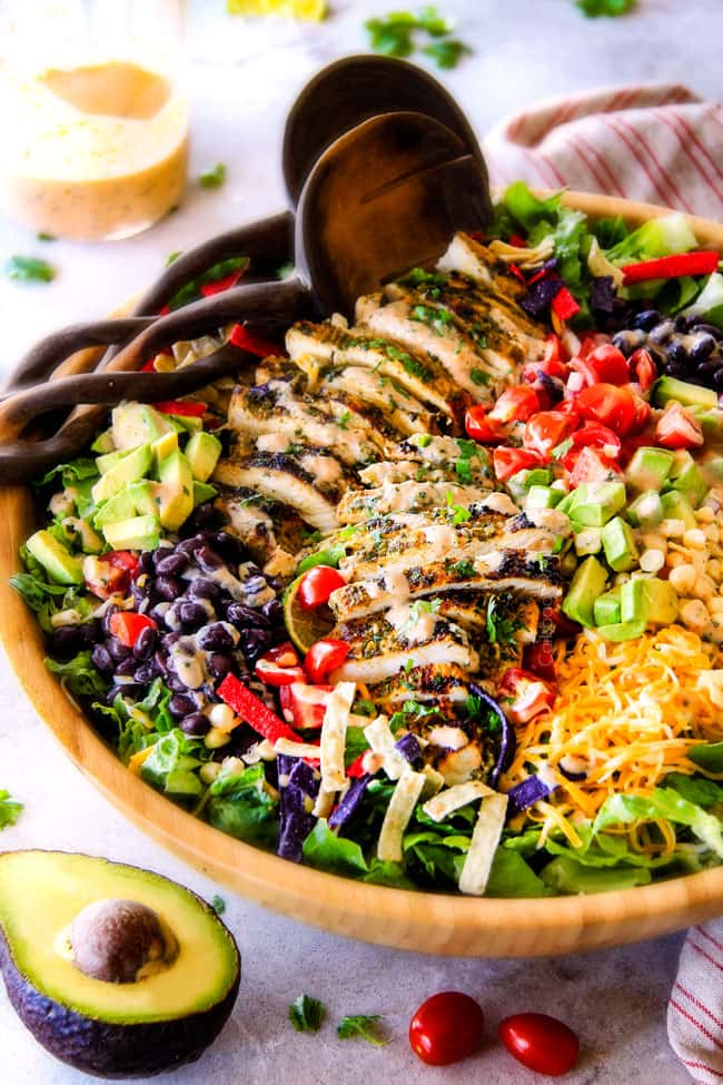 side view of best chicken taco salad in a wood bowl with black beans, corn, tomatoes, avocados, cheese and tortilla strips
