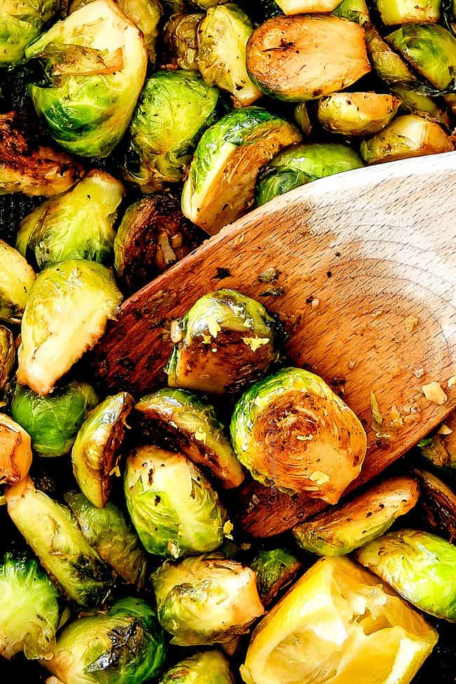top up close of crispy Sautéed Brussels Sprouts in a skillet with a wooden spoon
