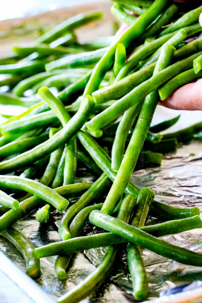showing how to make roasted green beans by tossing fresh green beans with olive oil, salt and pepper