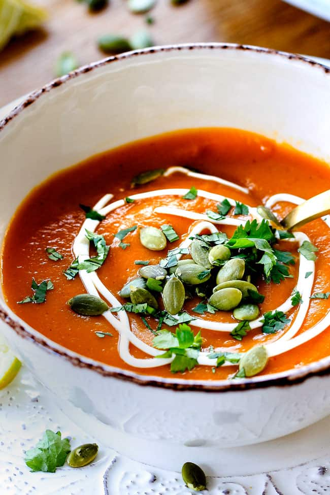 up close side view of a bowl of creamy sweet potato soup garnished with cilantro and seeds