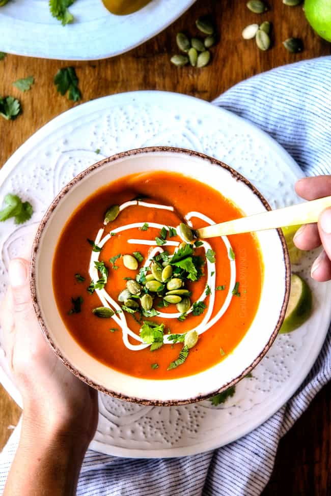 top view of two hands holding a bowl of savory Sweet Potato Soup