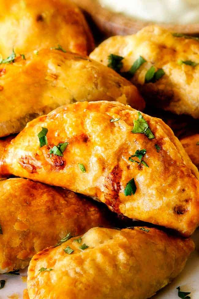 Freezer friendly, juicy, cheesy, shortcut Chipotle Chicken Empanadas doused in refreshingly Avocado Dip make the BEST crowd pleasing appetizers, dinners or snacks and can be made ahead of time and frozen for later!  The filling is to die for and the store bought puff pastry dough makes an easy shortcut for the buttery, flaky golden pastry!