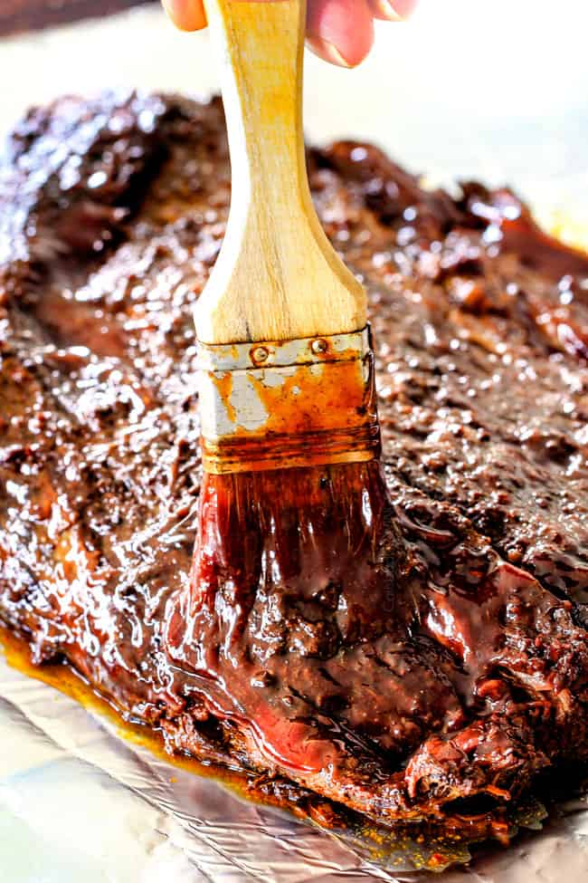 brushing bbq sauce onto piece of slow cooker brisket