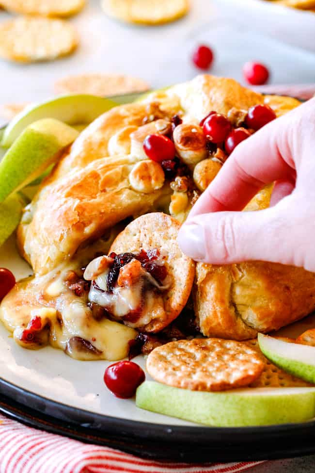 scooping a bite of baked brie in puff pastry with cranberries with a cracker