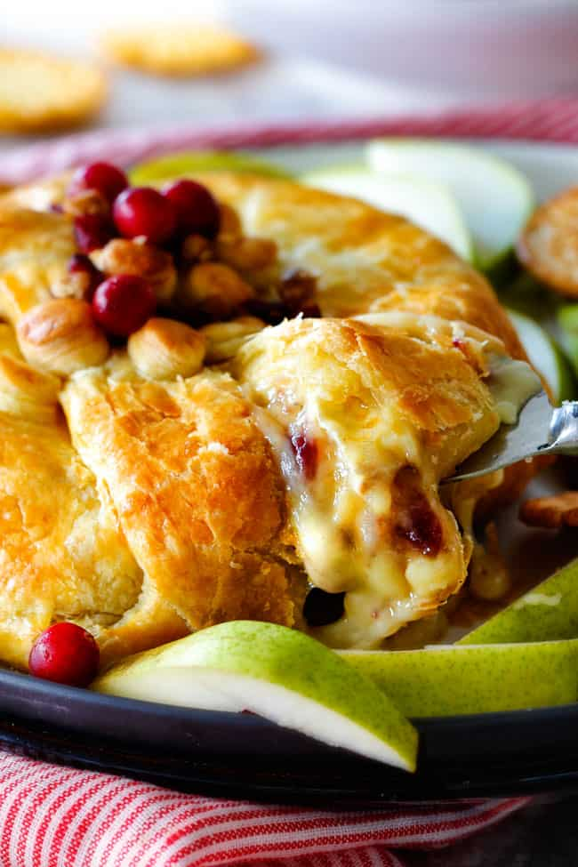 a serving spoon taking a slice of baked brie in puff pastry with cranberries and jam