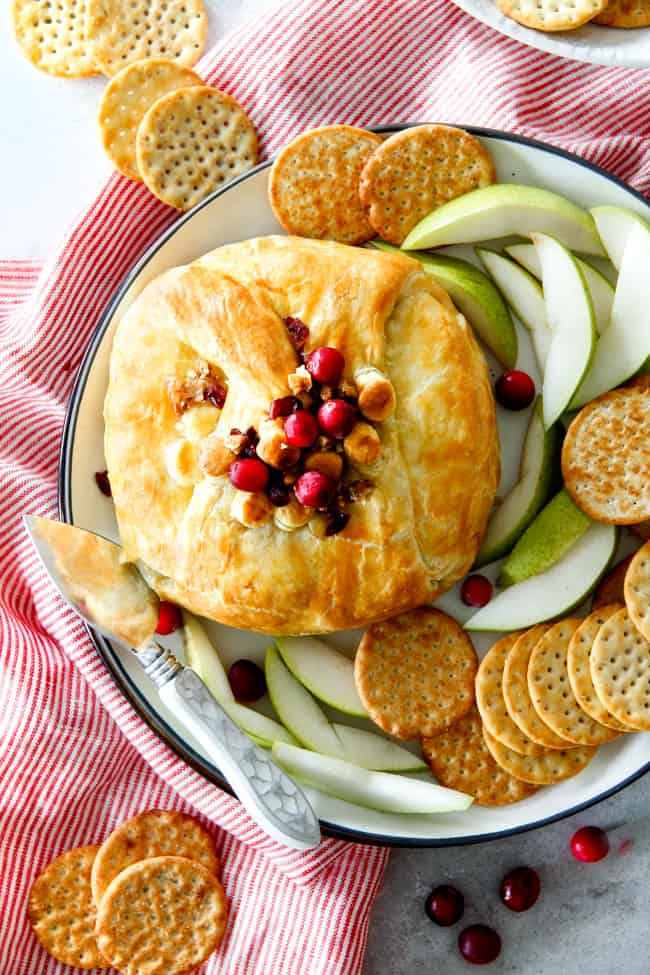 top view of baked brie in puff pastry with puff pastry served with crackers and apples