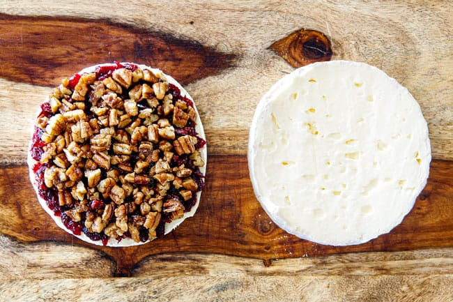 showing how to make baked brie in puff pastry by adding pecans to top of jam