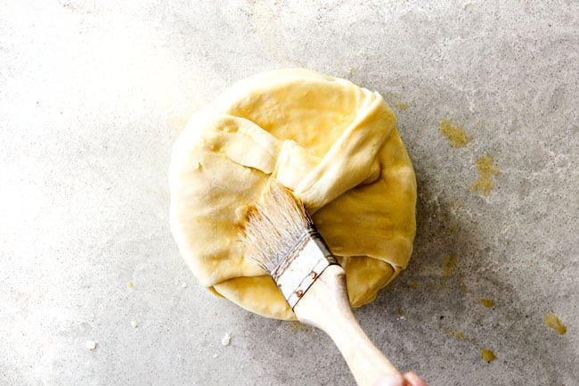 brushing baked brie in puff pastry with egg wash