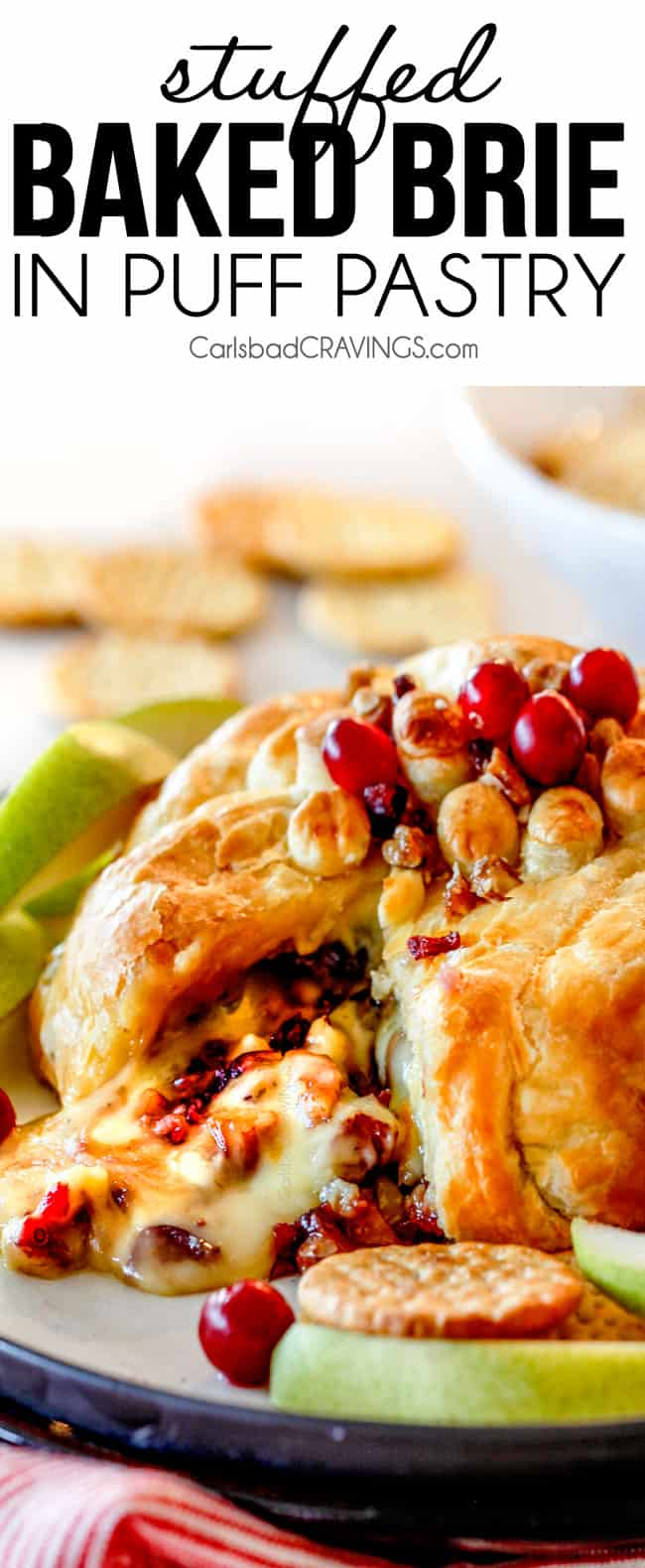 baked brie in puff pastry with with jam and cranberries oozing out of center