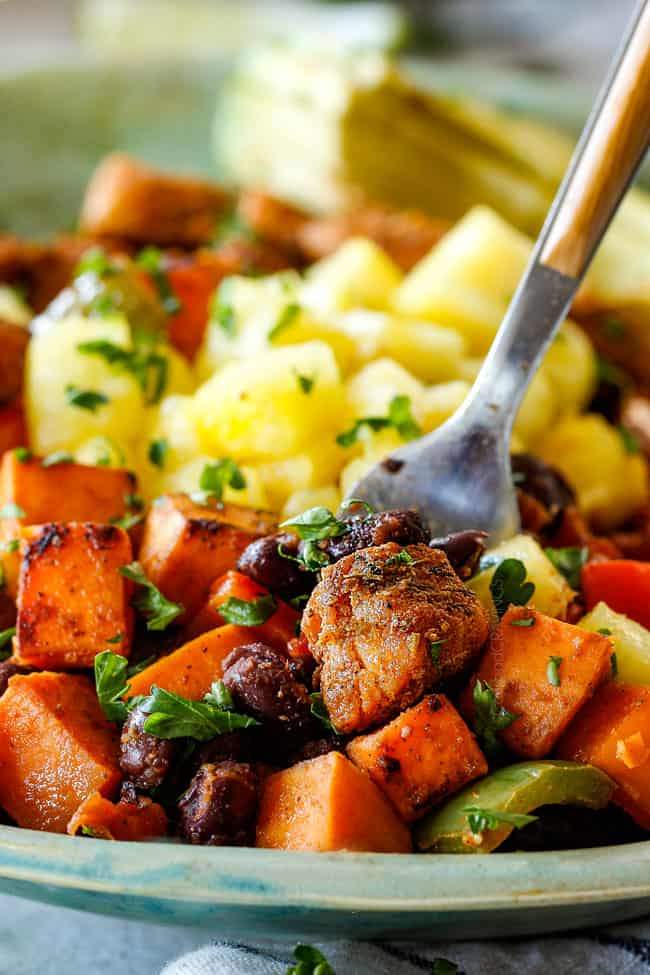 A spoon full of Cajun Chicken Black Bean Bowls with Avocado, Sweet Potatoes & Pineapple.