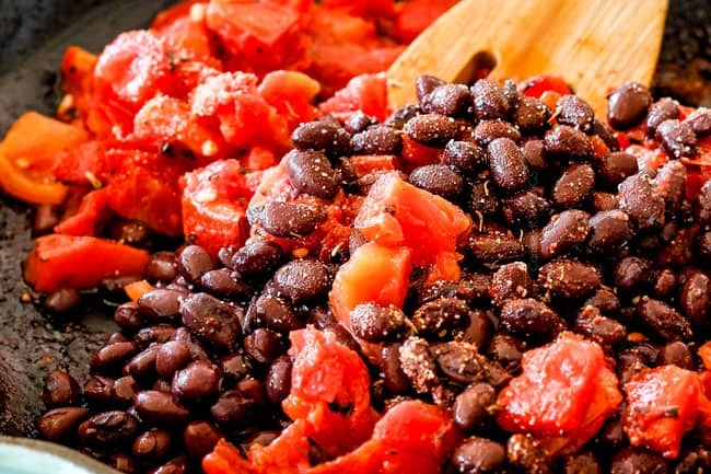 Mixing beand and tomatoes to make Cajun Chicken Black Bean Bowls with Avocado, Sweet Potatoes & Pineapple.