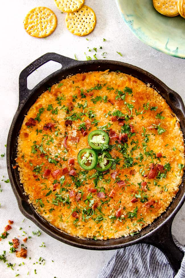 top view of Jalapeno Popper Dip with Bacon in a cast iron skillet with parsley and crackers