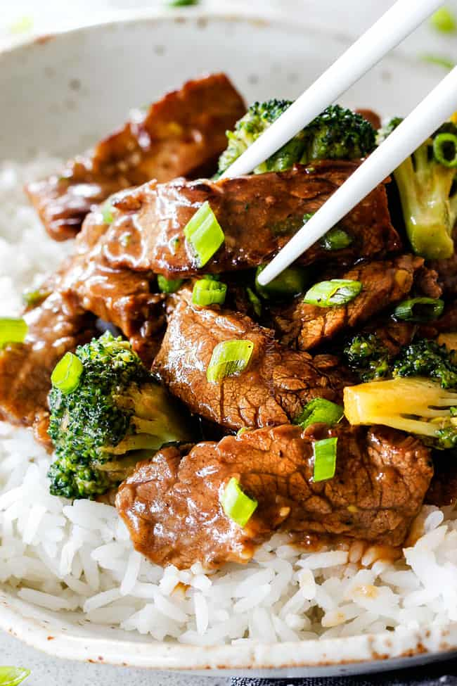 side view of beef broccoli with chopsticks picking up a piece of tender beef
