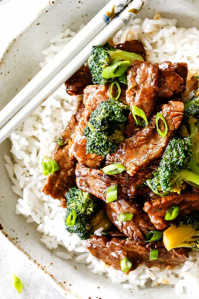 top view of best beef and broccoli recipe on white rice with green onions with chopsticks