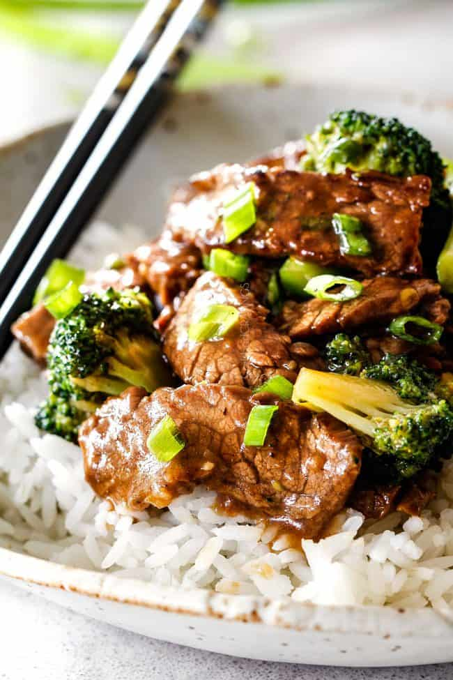 beef and broccoli with white rice and chopsticks