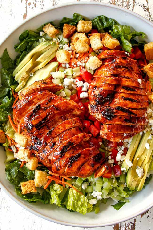 top view of Buffalo Chicken Salad in a white bowl with best buffalo chicken, blue cheese, celery, carrots, avocado, red bell peppers and lettuce
