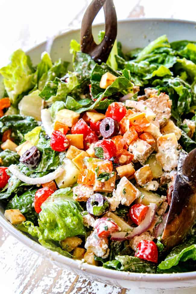 showing how to make Greek Chicken Salad by tossing romaine lettuce, Greek Chicken, red onions, olives, cucumbers, bell peppers, tomatoes and feta cheese together in a salad bowl