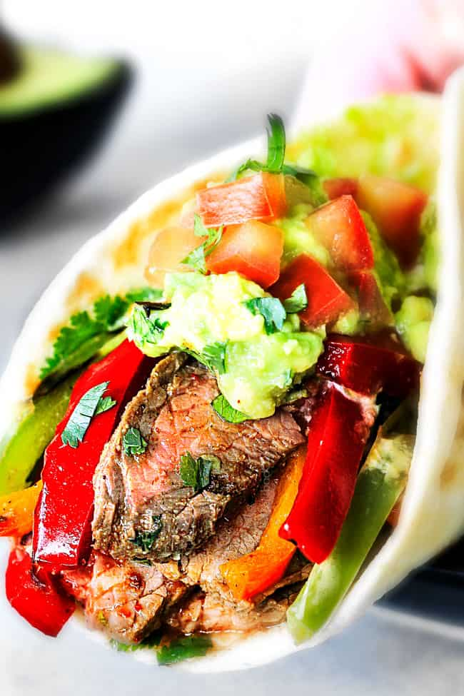 up close showing how to serve steak fajitas by wrapping up with steak, bell peppers, guacamole and pico de gallo