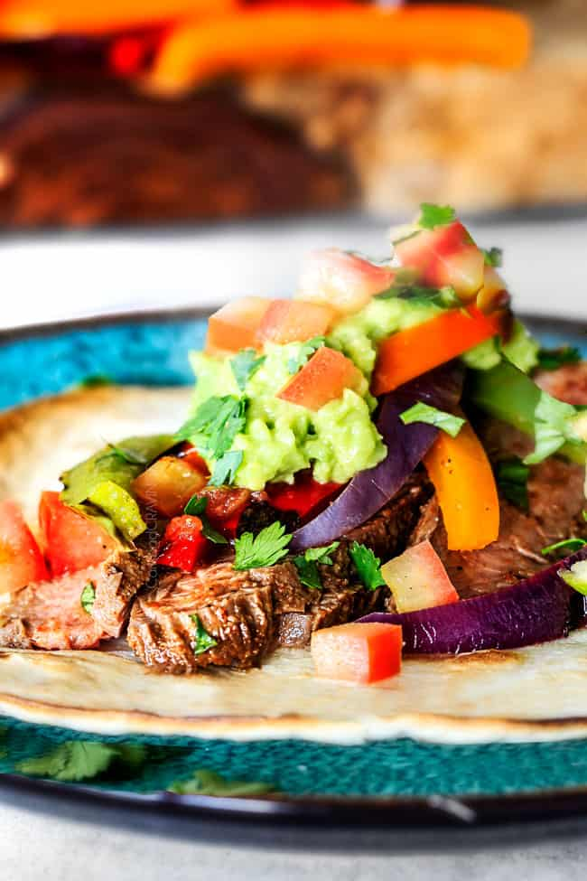 showing how to make steak fajitas by adding grilled steak on top of a flour tortilla with bell peppers, guacamole and pico de gallo