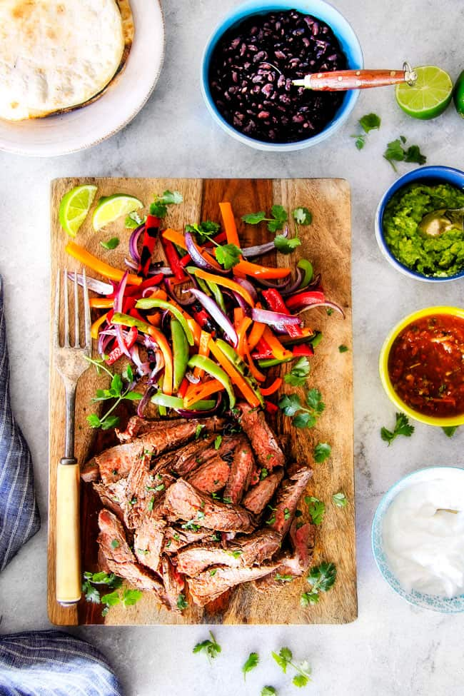 showing how to make steak fajitas by assembling sliced steak and bell peppers on a wood cutting board surrounded by toppings: cilantro, guacamole, salsa and sour cream