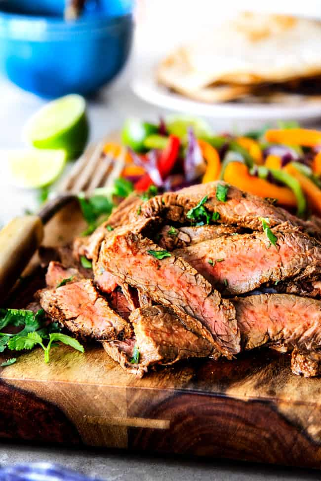 showing how to make steak fajitas by pilling thinly sliced steak and pepper on a wood cutting board