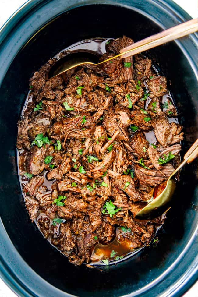 Shredded Chipotle Beef Barbacoa  serving with tongs.