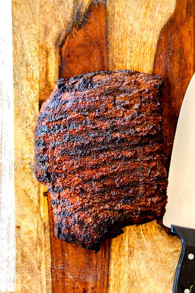 showing how to make grilled steak fajitas by letting steak rest on a wood cutting board before thinly slicing