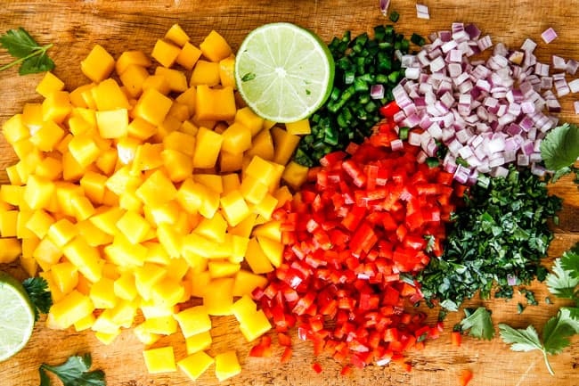 Mangos, red bell pepper, j alapeno, red onion, lime all chopped on a brown cutting board to make Mango Salsa for Cilantro Lime Shrimp Tacos