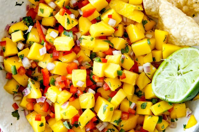 showing how to make easy Shrimp Tacos by adding Mango Salsa to a white bowl