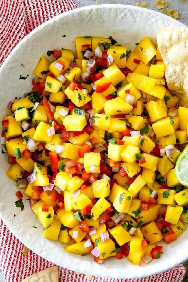showing how to make shrimp tacos by making mango salsa