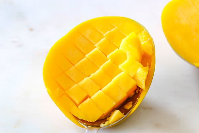 How to Cut A Mango showing scooping cubes of cut mango out with a spoon