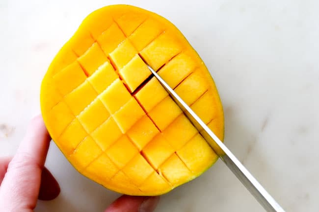 How to Cut A Mango showing cutting a grid pattern in mango flesh on a white cutting board