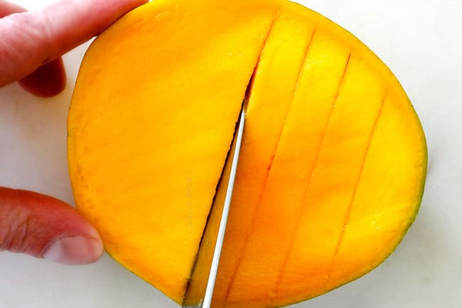 How to Cut A Mango showing slicing mango into vertical slices on a white cutting board