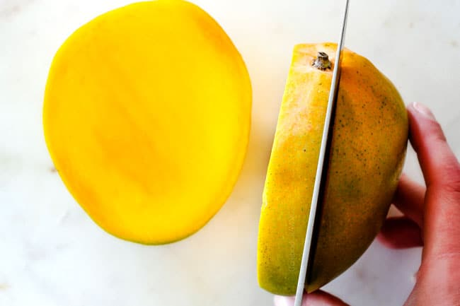 How to Cut A Mango showing cutting mango around stem on a white cutting board