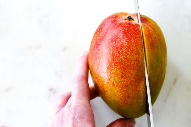 How to Cut A Mango showing locating stem to cut around it on a white cutting board