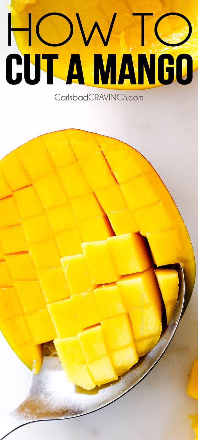 Showing How to Cut a mango with a mango on white cutting board with cubed cuts