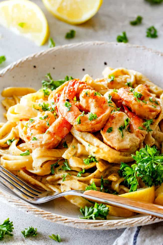 side view of lemon garlic shrimp pasta in white plate with fork