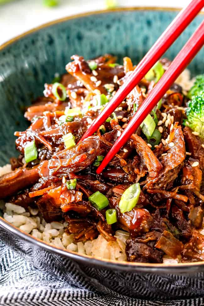up close of slow cooker Pulled Pork in green bowl with chopsticks