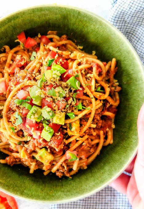 Twisting Taco spaghetti with a fork in a green bowl with cheese, avocados and tomatoes