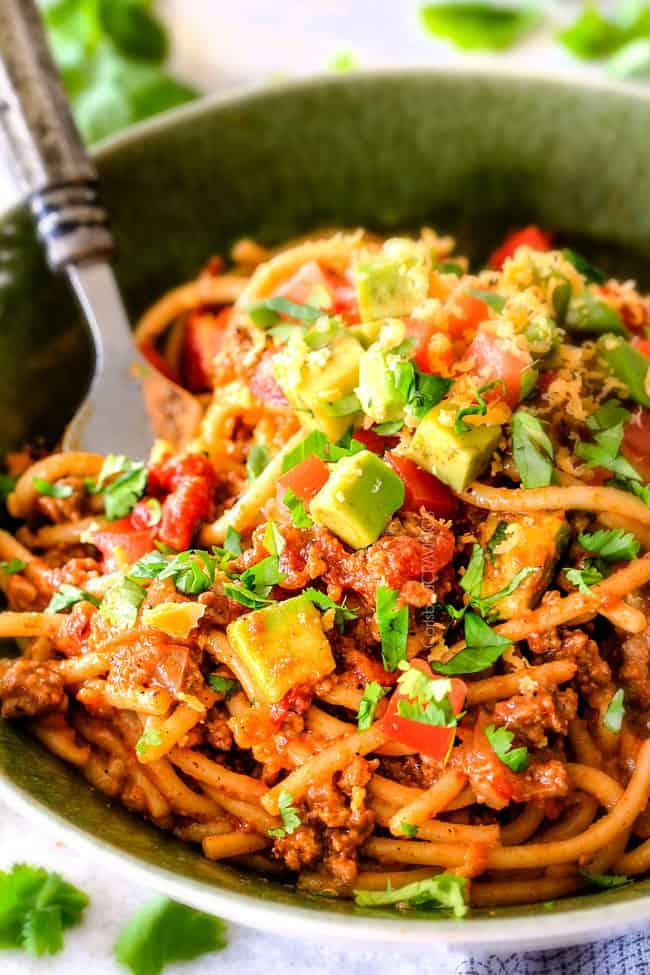 Adding spaghetti to Taco Spaghetti Sauce in a white large dutch oven