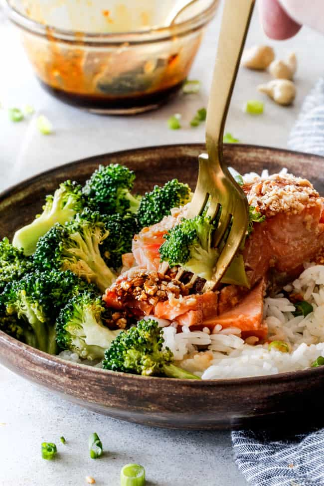 Fork in honey soy salmon with broccoli and rice in a brown bowl