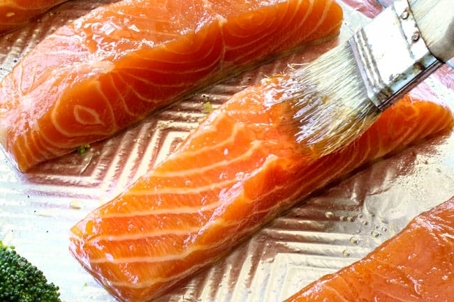 brushing salmon with honey on a baking sheet