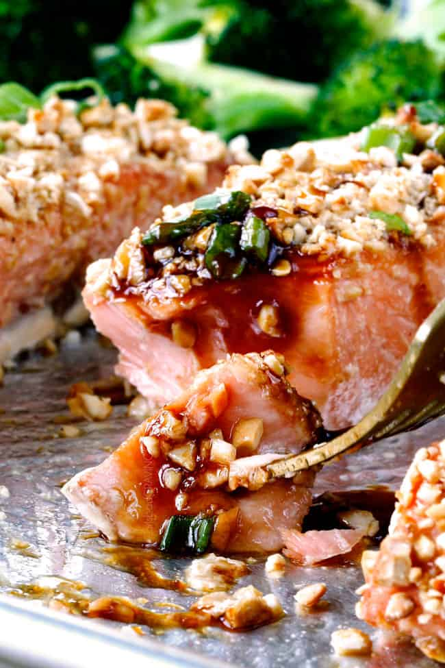Honey Soy Salmon crusted in cashews on a baking sheet with a fork