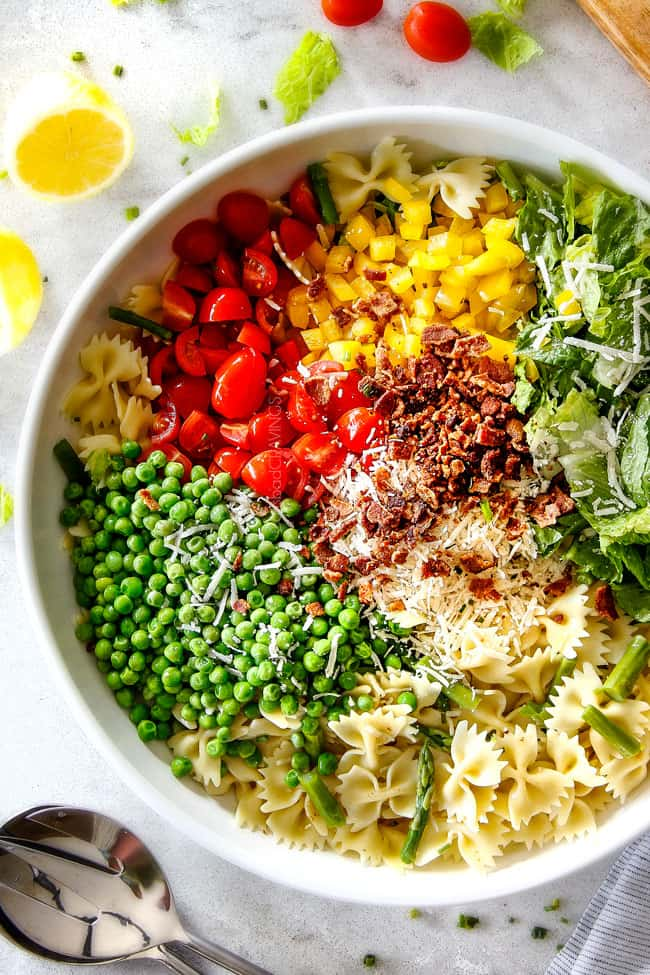 Showing how to make BLT Pasta Salad by layering pasta, bacon, lettuce, tomatoes, bell peppers, asparagus and peas in a large white bowl