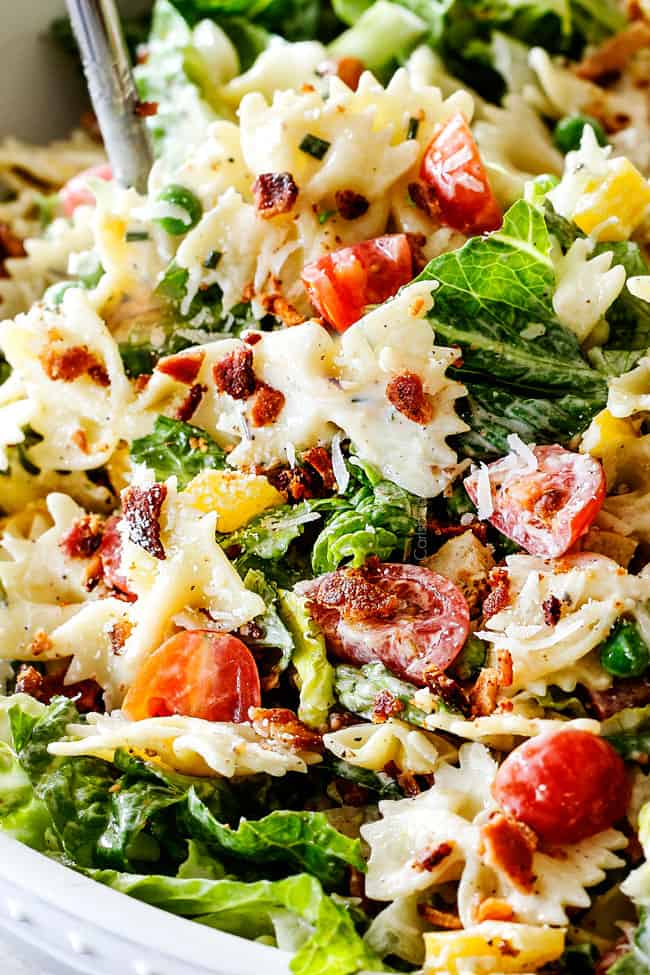 Up close side shot of easy BLT Pasta Salad recipe in a white bowl with tongs lifting salad up