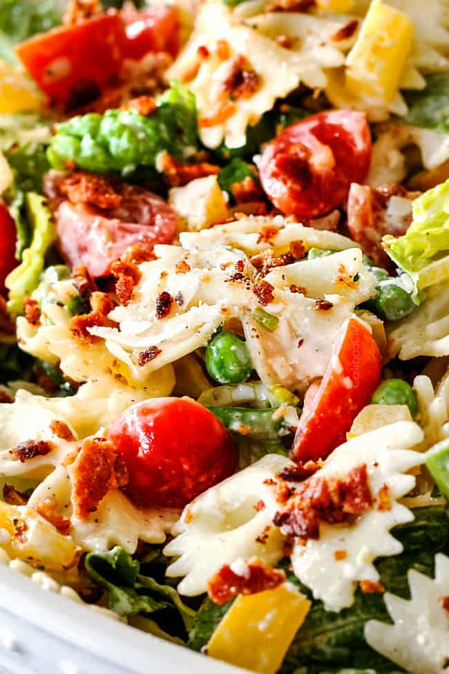 Up close side shot of easy BLT Pasta Salad recipe in a white bowl with one fork spearing pasta