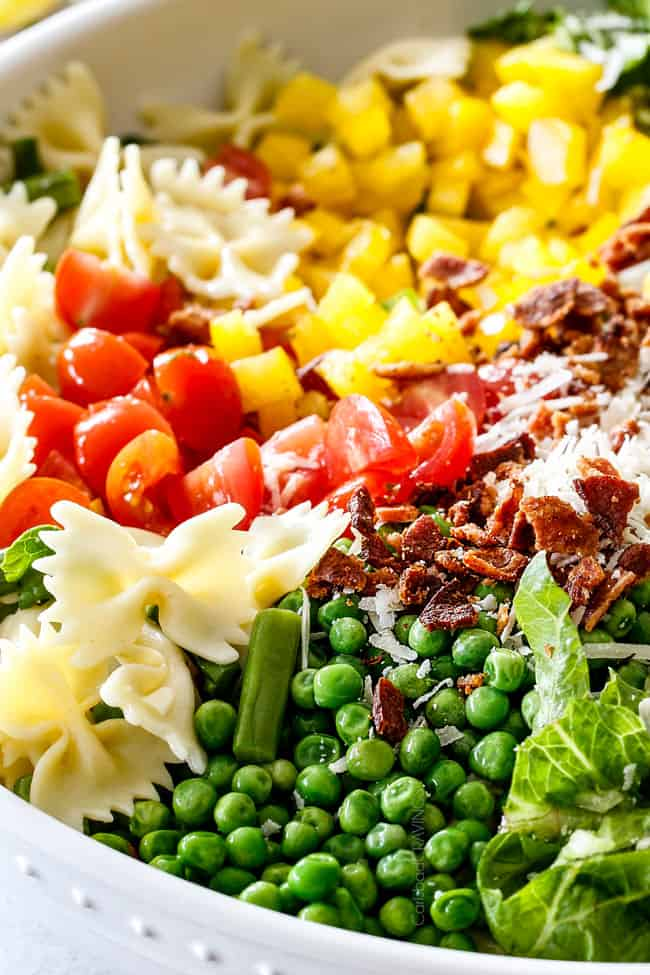 Up close of BLT Pasta Salad recipe ingredients of peas, pasta, bacon lettuce and tomatoes in a white bowl